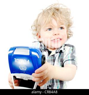 Niedliche kleine Junge spielt mit Polizeiauto vor weißem Hintergrund - Stockfoto