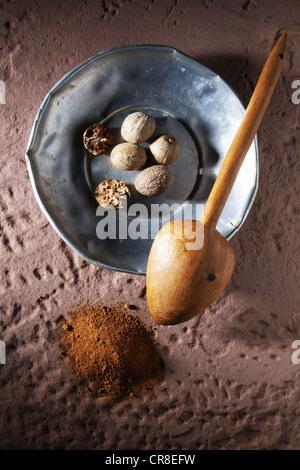 Muskatnüsse (Myristica Fragrans), auf einer Metallplatte mit einem Holzlöffel und Boden Muskatnuss auf einem rustikalen - Stockfoto