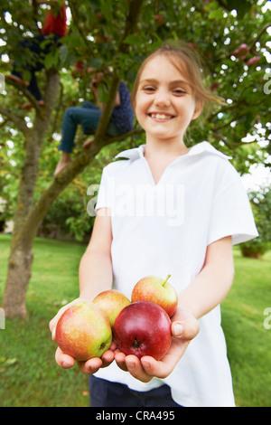 Lächelnde Mädchen halten Obst im freien - Stockfoto