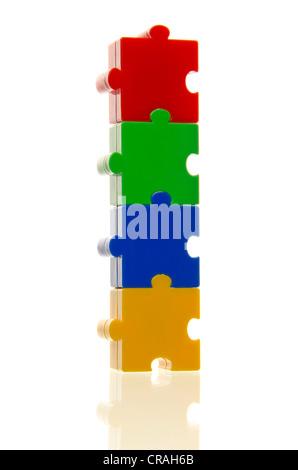 Vier bunte Puzzleteile fest übereinander, verbunden, symbolisches Bild für den Zusammenhalt - Stockfoto