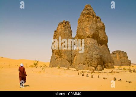 Mann zu Fuß in Richtung einer Felsformation in der Wüste Sahara, La Vache Qui Pleure, Algerien, Afrika - Stockfoto