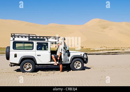 Mann mit einem Landrover Defender Geländewagen in den Feuchtgebieten von Sandwich Harbour, Namib-Naukluft-Nationalpark - Stockfoto