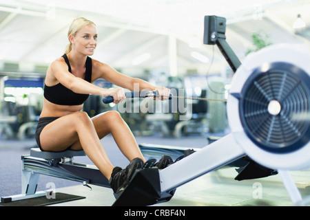 Frau mit Rudergerät im Fitness-Studio - Stockfoto