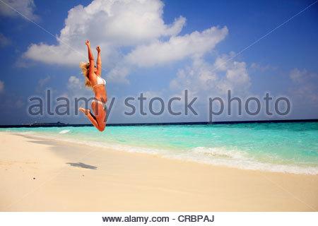Frau im Bikini am Strand vor Freude springen - Stockfoto