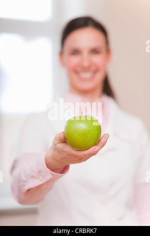 Lächelnde Arzt mit grünem Apfel - Stockfoto
