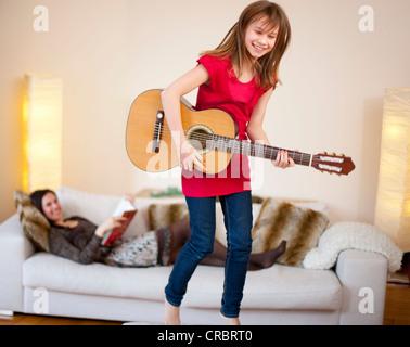 Mädchen spielt Gitarre im Wohnzimmer - Stockfoto