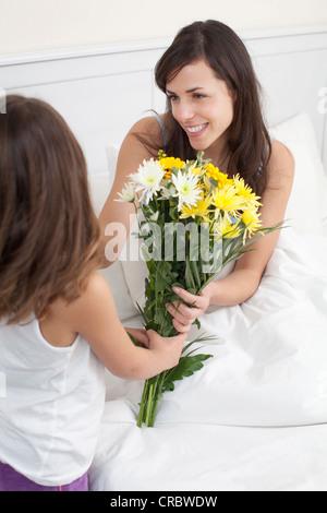 Mädchen bringen Mutter Blumenstrauß - Stockfoto