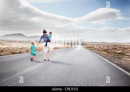 Familie gehen auf gepflasterte Landstraße - Stockfoto