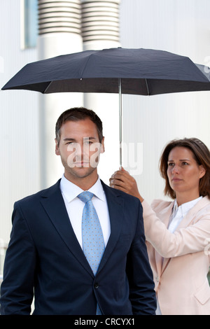 Geschäftsfrau Holding-Dach oberhalb Geschäftsmann - Stockfoto