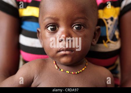 Ein Junge sitzt auf seiner Mutter Schoß an der Slipanlage Klinik in Monrovia, Liberia auf Montag, 2. April 2012 - Stockfoto