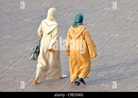 Zwei Frauen tragen traditionelle Djellabas Platz Djemaa El Fna, Medina oder Altstadt, UNESCO-Weltkulturerbe, Marrakesch - Stockfoto