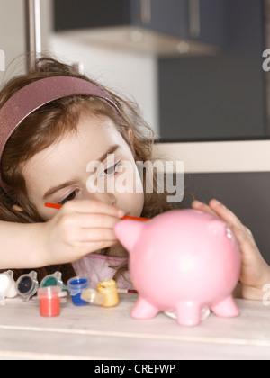 Mädchen-Malerei-Sparschwein - Stockfoto