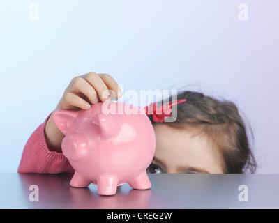 Mädchen, Münze in Sparschwein - Stockfoto