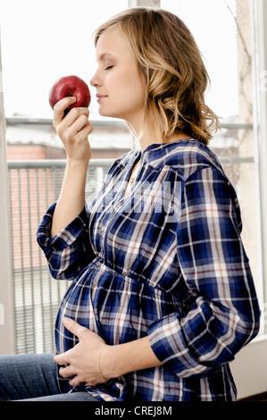 Lächelnd schwangere Frau riechende Apfel - Stockfoto