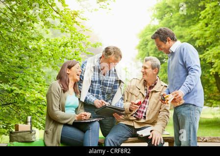 Tablet-Computer im Park mit Freunden - Stockfoto
