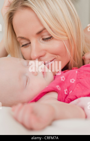 Mutter Babys Wange zu küssen, am Bett - Stockfoto
