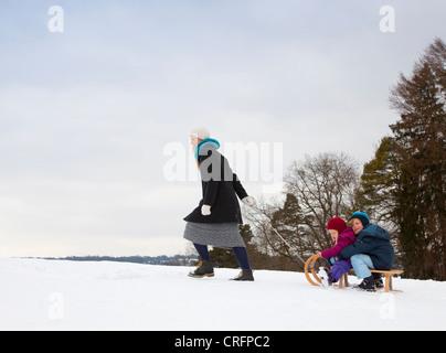 Mutter zieht Kinder auf Schlitten im Schnee - Stockfoto