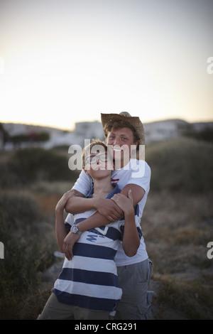 Lächelnde Brüder umarmen im freien - Stockfoto