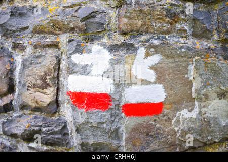 Richtungspfeil Schild an einer Steinmauer mit den weißen und roten Streifen ein Grande Randonnee Wanderweg. - Stockfoto