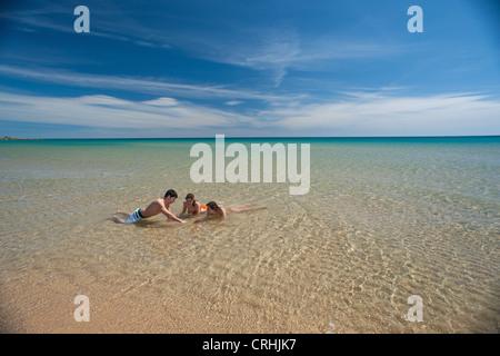 Freunde spielen in der Brandung am Strand - Stockfoto