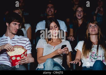 Frau mit Handy im Kino, Mann mit verärgert Ausdruck Blick - Stockfoto