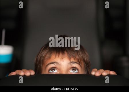 Junge spähen über Oberseite des Sitzes im Horror-Film im theater - Stockfoto