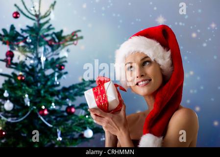 Frau trägt Weihnachtsmütze, schütteln Weihnachtsgeschenk - Stockfoto