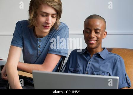 Junge Männer mit Laptop-Computer zusammen - Stockfoto