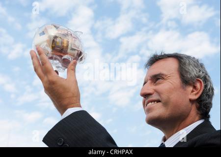 Reifer Mann halten transparente Sparschwein mit Euro gefüllt - Stockfoto