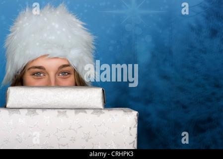 Junge Frau spähen über Stapel von Weihnachtsgeschenken, Porträt - Stockfoto