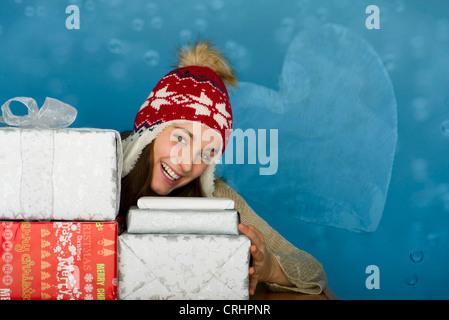 Junge Frau mit Stapeln von Weihnachtsgeschenken, Porträt - Stockfoto