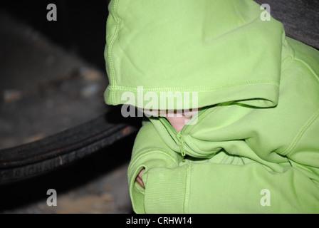 Angst vor kleinen Jungen, versteckt in seinen Pullover - Stockfoto