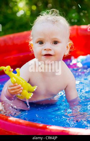 Kleinkind in aufblasbaren Pool Spielen - Stockfoto