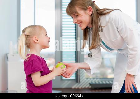 Arzt Übergabe Mädchen einen Apfel im Büro - Stockfoto