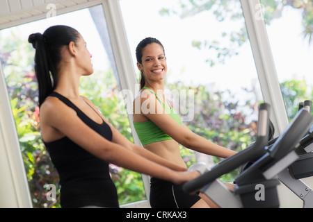 Junge Frauen reden und lachen während der Arbeit am Heimtrainer im Wellnessclub - Stockfoto