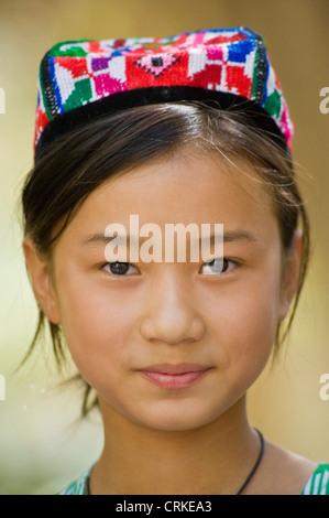Porträt eines lächelnden Uyghur chinesischen Mädchens in Tracht. - Stockfoto