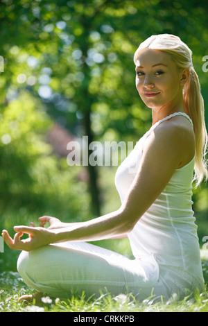 Eine junge Frau praktizieren Yoga außerhalb, auf Kamera - Stockfoto