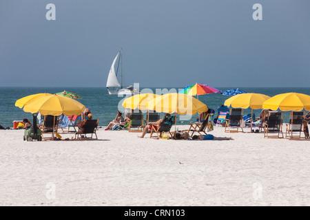 Gelbe Sonnenschirme, Segelboot und Sonnenanbeter, Clearwater Beach, FL - Stockfoto