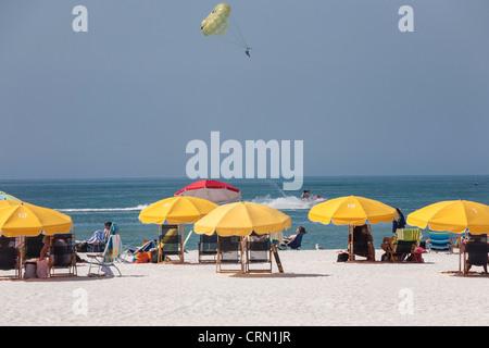 Gelbe Sonnenschirme, Para-Sailer und Sonnenanbeter, Clearwater Beach, FL - Stockfoto