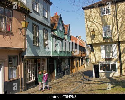 Paare, die auf dem Kopfsteinpflaster der Elm Hill von bunten Tudor Fachwerkbauten. - Stockfoto