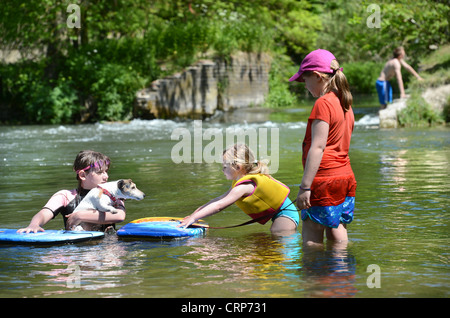 Drei Mädchen spielen mit ihrem Hund in den Fluss Avon im Figheldean Mühlenteich, Wiltshire UK - Stockfoto