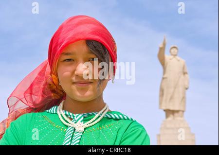 Eine junge Chinesin Uyghur posieren für die Kamera mit der Statue von Mao Zedong hinter in Kashgar. - Stockfoto
