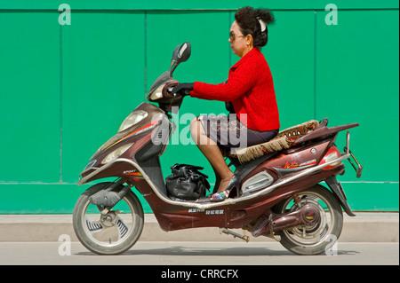 Eine chinesische Frau reist entlang einer Straße auf ihrem Roller in Kashgar. - Stockfoto