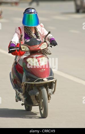 Eine chinesische Frau reist entlang einer Straße auf ihrem Roller in Kashgar eine Sonnenblende Schild tragen. - Stockfoto