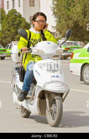 Eine chinesische Frau reist entlang einer Straße auf ihrem Roller beim Telefonieren mit ihrem Handy in Kashgar. - Stockfoto