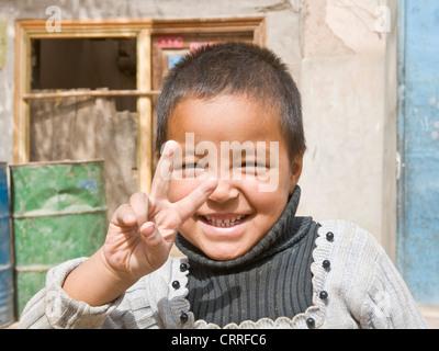 Uyghur chinesische junge posiert für die Kamera auf der Straße in der alten Stadt Kashgar. - Stockfoto