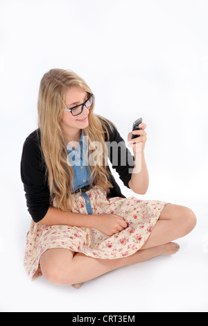 Junge Frau sitzt allein lesen einer Nachricht auf ihr Handy. Isoliert auf weißem Hintergrund. - Stockfoto