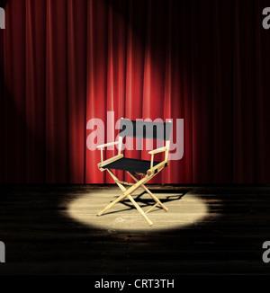 Ein Regiestuhl auf einer Bühne mit einem roten Vorhang und spotlight - Stockfoto