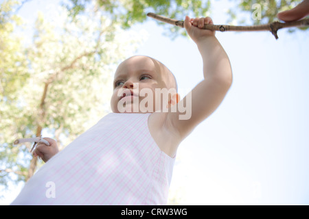Einjähriges Mädchen hält einen Stock und im freien laufen lernen. - Stockfoto