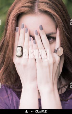 Junge Frau mit roten Haaren, die Hände vor das Gesicht halten - Stockfoto
